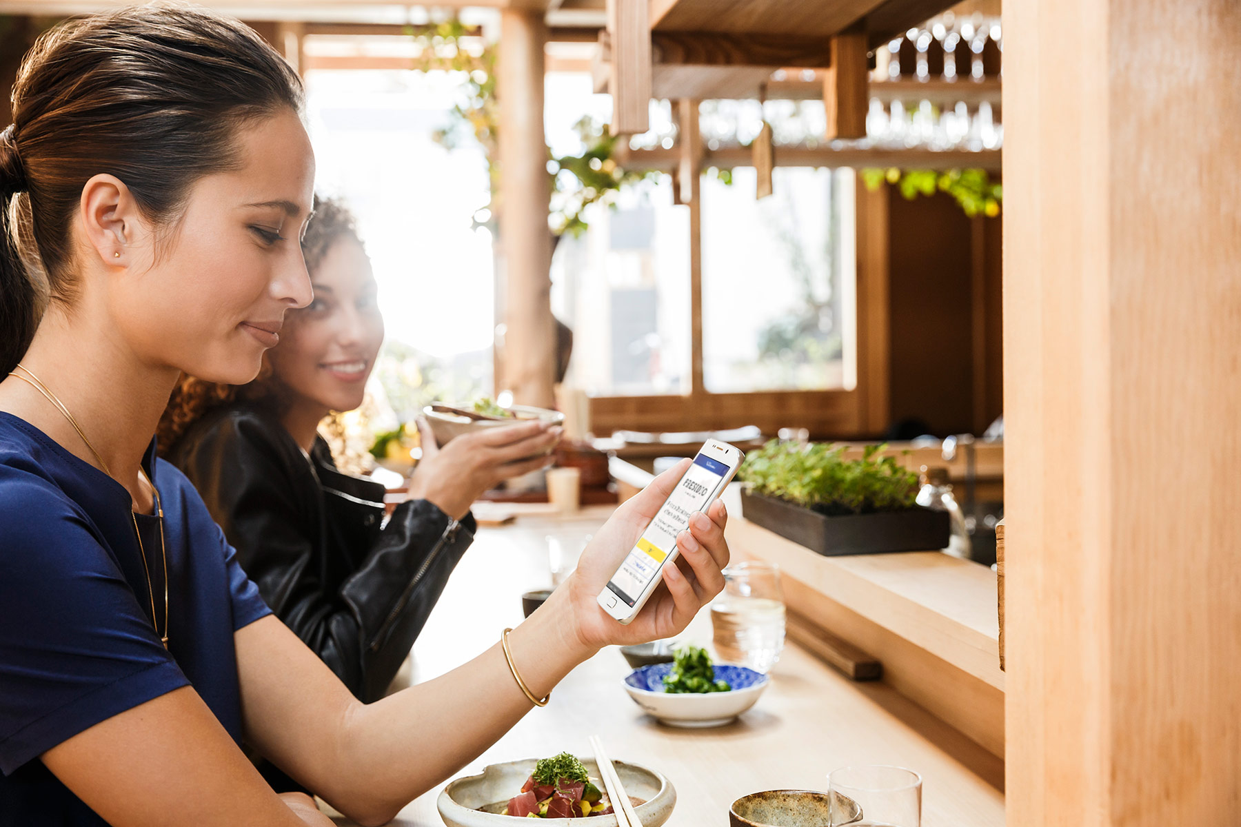 Woman seated at the bar with a friend at a restaurant smiling down at her phone.